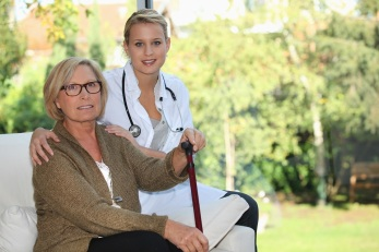 Elderly woman and young female caregiver at home