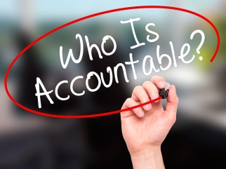 Man Hand writing Who Is Accountable? with black marker on visual